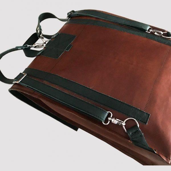 Lederrucksack braun mit grünen Schulterriemen und Tragegriff, handmade.