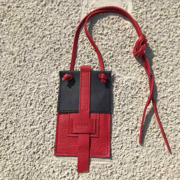 Perfekte Ledertasche für dein Handy. Die Karten kommen ins Außenfach, Geld oder Schlüssel ins Innenfach. Aus schwarzem und roten Rindsleder.