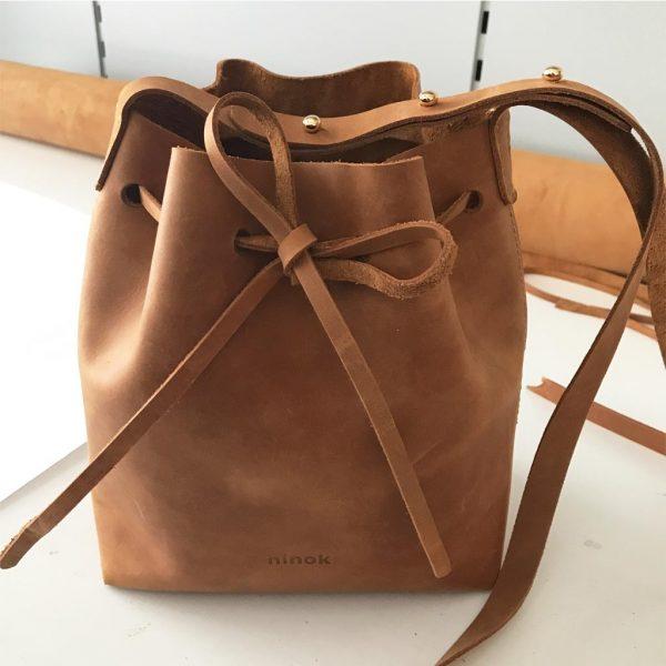 Cognac braune Umhängetasche aus Leder. Mittelgroße Bucket Bag mit Zugverschluss. Verstellbarer Lederriemen.