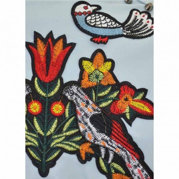 Nevada Love Paris Kunst Lederjacke mit Spitz und Sternen Nieten und Applikationen. Gestickte Insekten, Vogel und Blumen Patches. Mit Reißverschlüssen. Hellblaue Damenjacke in Große S 38.